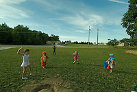 Five costumed children play in the front yard of a rural home.