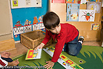 Education preschoool children ages 3-5 floor puzzle boy working on long alphabet puzzle horizontal