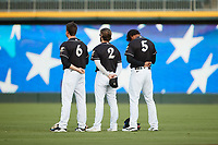 (L-R) Charlotte Knights outfielders Blake Rutherford (6), Luis Gonzalez (2), and Nick Williams (5) stand for the National Anthem prior to the game against the Gwinnett Stripers at Truist Field on July 15, 2021 in Charlotte, North Carolina. (Brian Westerholt/Four Seam Images)