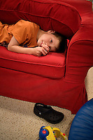 """Jack Ursitii, age 7, plays on a couch during a """"sensory break"""" in his home in Dover, Mass., on Monday, July 25, 2011. His teacher, Sarah Hoey from the Nashoba Learning Group, """"squishes"""" Jack with a couch cushion, which is a favorite activity of Jack's. Jack has been diagnosed with autism.  After school at his home, Jack works with his teacher and a therapist to do educational and independent leisure activities. Periodically Jack takes """"sensory breaks"""" to stop activity and play independently, allowing him to return to his tasks with greater concentration. During the """"sensory breaks"""" Jack does a variety of things, including looking at his reflection, making faces, jumping on a small trampoline or cushions, or play with an iPad...Jack Ursitti wears a small GPS ankle bracelet at all times in case he runs off from his family or caretakers. The device will be activated if he goes missing, allowing police and other searchers to find him."""