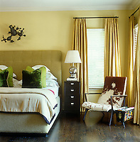 Varying tones of green, from the olive green upholstered headboard to the deep green scatter cushions on the bed, constrast with the pale ochre walls of this bedroom