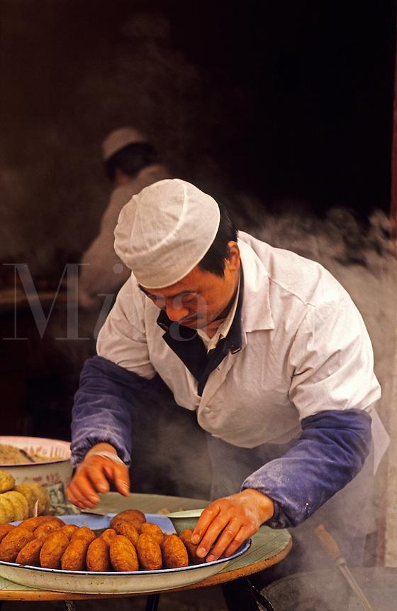 China. Xi'an. Xian.  Cook making rissoles in pavement/sidewalk restaurant..