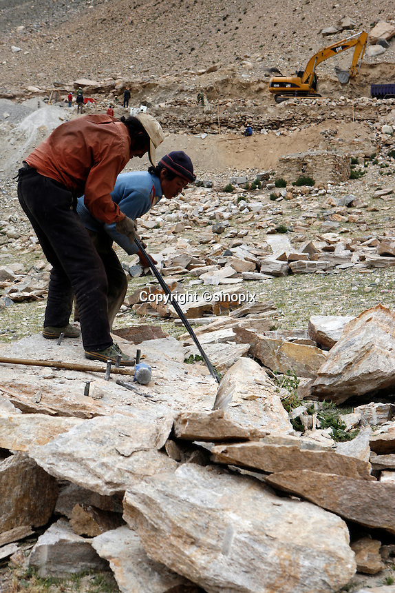 """China started building a controversial 67-mile """"paved highway fenced with undulating guardrails"""" to Mount Qomolangma, known in the west as Mount Everest, to help facilitate next year's Olympic Games torch relay./// Tibetan men break rocks with sledge hammers to build the road to Everest Base Camp. <br /> Tibet, China<br /> July, 2007"""