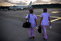 'Twin Teachers' Rian and Rossy on their way to the plane that will fly them to a remote village in Indonesia's Papua province to visit students from one of their schools. Since the early 1990s, twin sisters Sri Rosyati (known as Rossy) and Sri Irianingsih (known as Rian) have used their family inheritance to set up and run 64 schools in different parts of Indonesia, providing primary education combined with practical skills to some of the country's most deprived children.