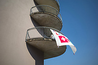 """Switzerland. Canton Ticino. Ponte Tresa. The inhabitants on the building's first floor have written a message on a white sheet hanged outside on their balcony which faces  Italy. The words say """" Together we will make it. Switzerland and Italy"""". The flag of Switzerland displays a white cross in the centre of a square red field. The white cross is known as the Swiss cross. A woman is hanging wet clean clothes on the dryer. Due to the spread of the coronavirus (also called Covid-19)., the Federal Council has categorised the situation in the country as """"extraordinary"""". It has issued a recommendation to all citizens to stay at home, especially the sick and the elderly. From March 16 the government ramped up its response to the widening pandemic, ordering the closure of borders, bars, restaurants, sports facilities and cultural spaces. Only businesses providing essential goods to the population – such as grocery stores, bakeries and pharmacies – are to remain open. Ponte Tresa is a municipality in the district of Lugano. 7.04.2020 © 2020 Didier Ruef"""