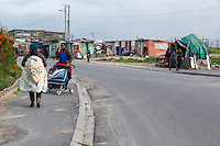 South Africa, Cape Town, Guguletu Township Street Scene.  Woman Carrying Baby on Back, Woman Pushing Baby in a Pram (Baby Buggy).