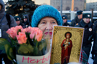 A woman holds flowers and a religious icon in front of police in Lubyanka Square during an unsanctioned anti-Putin demonstration in Moscow, Russia.  Police arrested a number of protesters and opposition leaders.