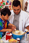 4 year old boy with father cooking and baking in kitchen vertical leveling off measuring flour