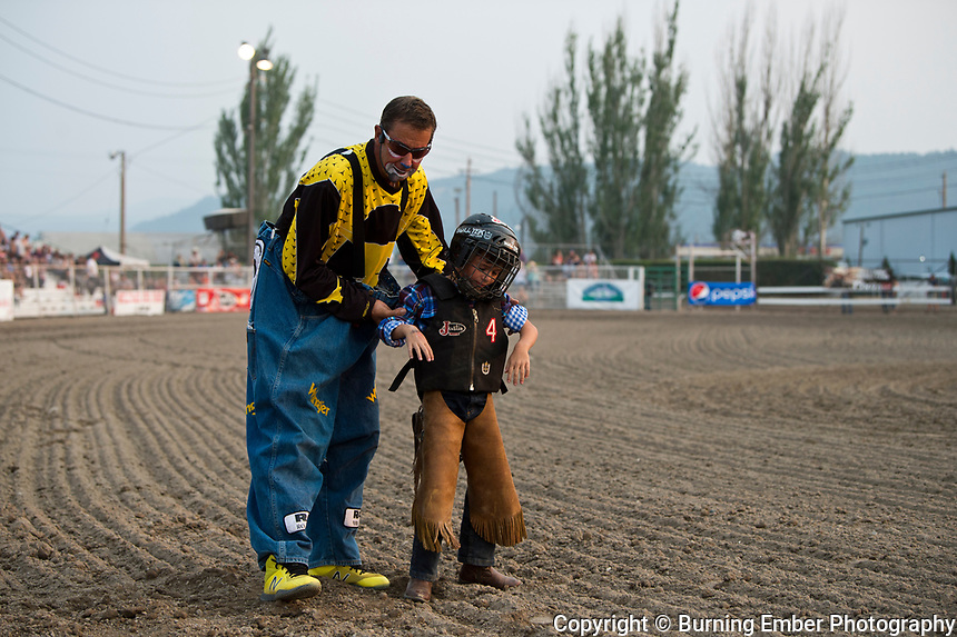 Dennis Halstead helps up a contestant during the Mutton Bustin event during the 3rd perf at the Northwest Montana Fair and  Rodeo Kalispell MT August 18th, 2018.  Photo by Josh Homer/Burning Ember Photography.  Photo credit must be given on all uses.