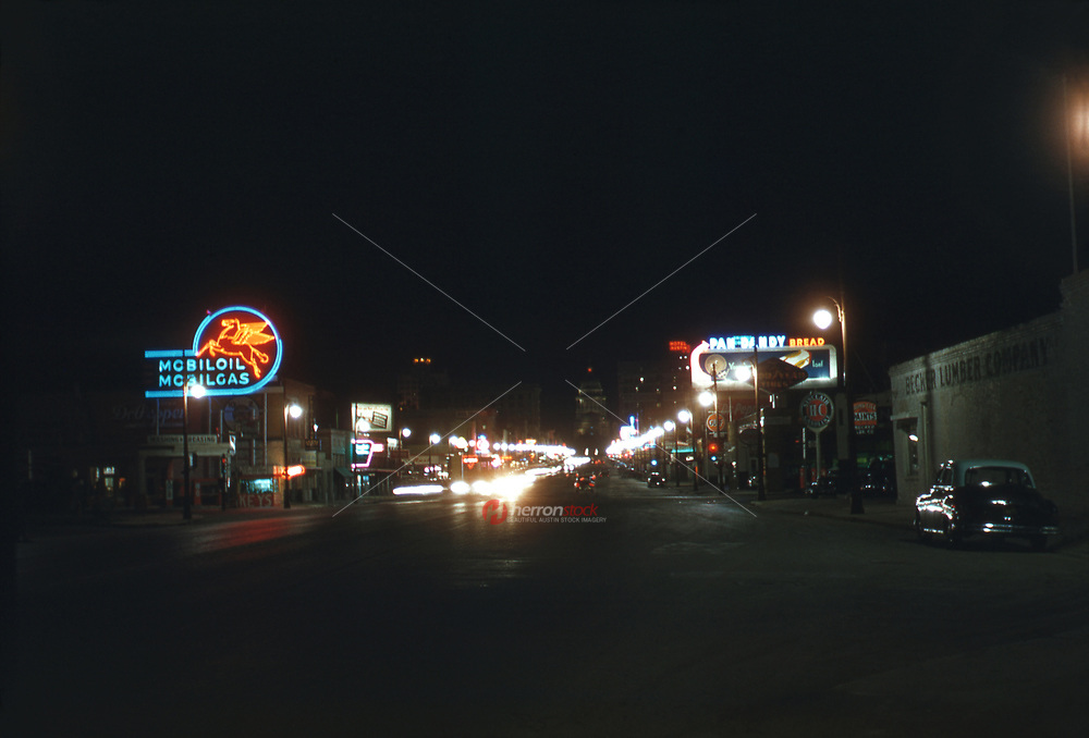 Unique nighttime view of retail shops and gas stations and the State Capitol as seen from north Congress Avenue looking south to downtown Austin, 1954.<br /> <br /> Congress Avenue is a major thoroughfare in Austin, Texas. The street is a six-lane, tree lined avenue that cuts through the middle of the city from far south Austin and goes over Lady Bird Lake leading to the Texas State Capitol in the heart of Downtown.<br /> <br /> Congress Avenue south of Lady Bird Lake is known as South Congress, often abbreviated to SoCo, and is an increasingly popular shopping and rental district. It passes the historic Travis Heights neighborhood, the Texas School for the Deaf, and St. Edward's University as it passes south out of town.