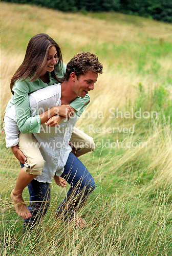Young man giving a woman a piggy back ride..