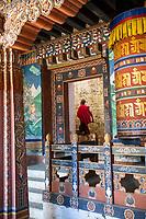 Trongsa, Bhutan.  Young Buddhist Monk Entering an Inner Courtyard in The Trongsa Dzong (Monastery-Fortress).  Prayer Wheel alongside Entrance.