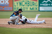 Yordys Valdes (7) of the Lynchburg Hillcats slides into third base ahead of the tag by Reivaj Gacia (1) of the Myrtle Beach Pelicans at Bank of the James Stadium on May 23, 2021 in Lynchburg, Virginia. (Brian Westerholt/Four Seam Images)
