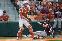 Texas Longhorns catcher Jacob Felts #12 watches as Texas A&M runner Scott Arthur #14 slides home in the NCAA baseball game against the Texas A&M Aggies on April 28, 2012 at UFCU Disch-Falk Field in Austin, Texas. The Aggies beat the Longhorns 12-4. (Andrew Woolley / Four Seam Images).