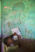 Ethiopia. Southern Nations, Nationalities, and Peoples' Region. Omo Valley. Hayzo Village. High altitude: 2800 meters. Dorze tribe. A young boy writes words in his notebook leaning against the wall of a public school's classroom. The Dorze are a small ethnic group inhabiting the Gamo Gofa Zone who speak the Dorze language, an Omotic tongue. The Dorze are predominantly agriculturalists living in permanent villages. The Dorze numbered 40'000 reside in villages near the cities of Chencha and Arba Minch. Southern Nations, Nationalities, and Peoples' Region (often abbreviated as SNNPR) is one of the nine ethnic divisions of Ethiopia. 6.11.15 © 2015 Didier Ruef
