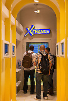 Young travelers exchange currency at an automated exchane booth, Rome, Italy.
