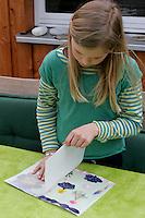 Kinder basteln ein Fensterbild mit Blüten, Mädchen klebt zweites Pergamentpapier auf das mit Blüten beklebte Pergamentpapier