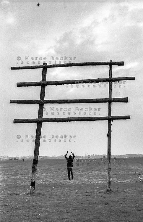 Berlino, aeroporto di Tempelhof riqualificato a parco pubblico. Una struttura formata da pali in legno e un ragazzo con aquilone --- Berlin, Tempelhof airport requalified to public park. A structure made of wooden poles and a young man with kite
