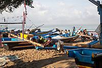 Bali, Indonesia.  Bringing a Fishing Boat up on Shore.  Jimbaran.