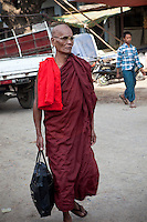 Myanmar, Burma.  Mandalay.  Buddhist Monk Walking.  Monks shave their heads.
