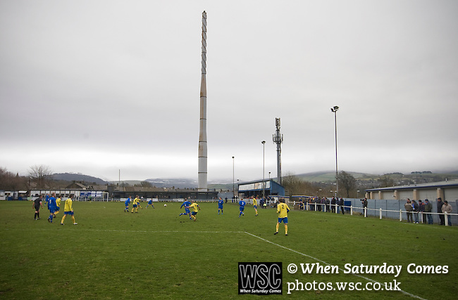 Glossop North End 0 Barnoldswick Town 1, 19/02/2011. Surrey Street, North West Counties League Premier Division. Glossop North End (blue strips) in action action as their club play Barnoldswick Town in the Vodkat North West Counties League premier division at the Surrey Street ground with a disused steel works chimney visible in the background. The visitors won the match by one goal to nil watched by a crowd of 203 spectators. Glossop North End celebrated their 125th anniversary in 2011 and were once members of the Football League in England, spending one season in the top division in 1899-00. Photo by Colin McPherson.