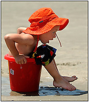 Oops. A child gets his bottom stuck after he tried to sit on the open side of a bucket during a vacation to the beach. Photo taken on Sullivan's Island, near Charleston, SC.  Model released image.