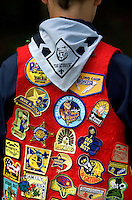 A cub scout shows off his red vest filled with scouting patches.