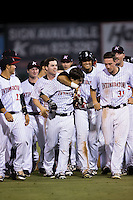 Grant Massey (18) is congratulated by his teammates after defeating the Asheville Tourists with a walk-off single in the bottom of the tenth inning at Intimidators Stadium on May 28, 2016 in Kannapolis, North Carolina.  The Intimidators defeated the Tourists 5-4 in 10 innings.  (Brian Westerholt/Four Seam Images)