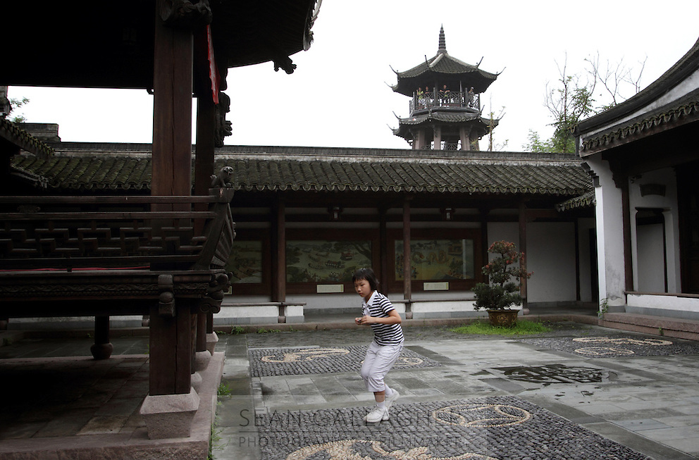 A girl in a temple in the Xixi wetlands which lie in the west of the city of Hangzhou. This is China's 'first national wetland park,' dubbed as such to act as a role model to all other wetlands in China and to supposedly show how to effectively manage and restore wetlands, notably urban wetlands. Zhejiang Province. China. 2010