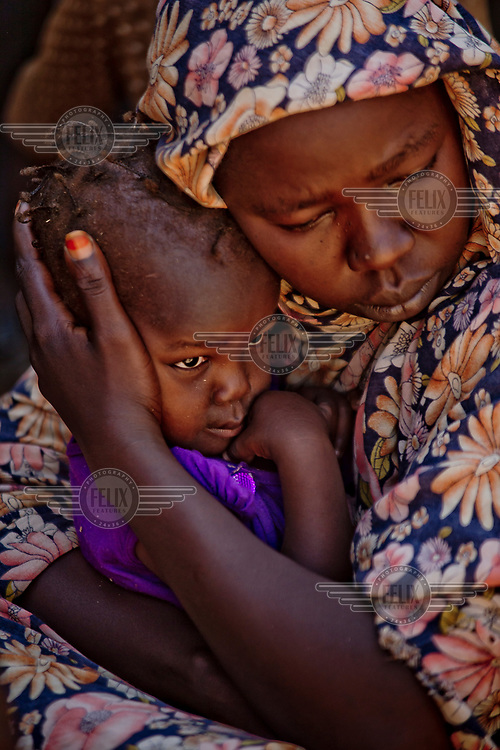 Namal Ali Dut (24) holds her daughter, Oma Hassan Jalewa (2), years in her arms. She is the mother of two (the other is a boy) whose husband has died. She was already an IDP in South Sudan and is now at the Dzaipi transit camp but says she is desperate as she has no tent or any idea of how to get food.