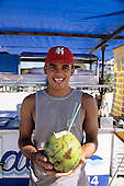 Sao Vicente, Brazil. Laughing young man in baseball cap serving a coconut at a beach bar.