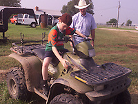 Arkansas Democrat-Gazette/ Bob Coleman--John McDonnell teaches his nephew Michael McDonnell, 12, how to drive an ATV on the ranch. Michael and his father Patrick were visiting John. They are both from Ireland.