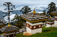 The memorial choetens (stupas) at the Dochu La Pass at 3,100m elevation looking towards the raincloud covered Himalayas. There are 108 memorial choetens on this elevated highway between Thimpu and Punakha.
