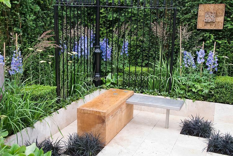 Modern upscale white city urban patio with black mondo grass Ophiopogon, black fence, low wall, boxwood Buxus, blue Delphinium, garden bench