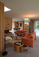 The open plan living area is furnished with a pair of sofas by Vico Magistretti