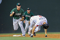 Left fielder Mike Myers (2) twists his ankle as he is caught in a rundown by shortstop Jeremy Sy (2) of the Augusta GreenJackets in a game on Opening Day, Thursday, April 9, 2015, at Fluor Field at the West End in Greenville, South Carolina. (Tom Priddy/Four Seam Images)