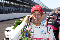 30th May 2021, Indianapolis, Indiana, USA; NTT Indy Car Series driver Helio Castroneves talks on his cell phone after winning the 105th running of the Indianapolis 500 on May 30, 2021 at the Indianapolis Motor Speedway in Indianapolis, Indiana.