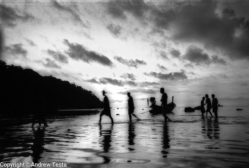 """Moken men arrive for work at the headquarters of the Surin National Park ..The Moken are a nomadic tribe who live on the Surin Islands islands 60 km off the coast of Thailand. Recent scientific studies have shown that the underwater eyesight of Moken children is more than50% percent better than the underwater eyesight of other children. Scientists believe that the Moken train their eyes to see better out of necessity, they have to hunt for fish, and also make out things on the sea bed far below them. Experiments are now underway in Sweden to see if other children can train their eyes in a similar way. The Moken spend a large part of their time in the sea, and seem almost as at home in that environment as on land. At present they have no Family names or citizensip, but the Thai authorities have proposed that they all be given the same second name, roughly translated it means """"Hero of the Sea"""". The entire Moken population of the Surin Islands survived the recent Tsunami. News reports say that by the time the waves crashed ashore, the Moken were already on the higher ground and therefore safe. According to interviews they relied on the sayings of their ancestors which have been passed down through generations (they have no written language) which warn of the sea disappearing and then returning with a terrible force."""