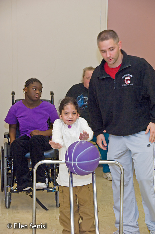 MR / Albany, NY.Langan School at Center for Disability Services .Ungraded private school which serves individuals with multiple disabilities.Physical education teacher supervises student as he pushes ball down ramp in Adaptive Physical Education class (APE). Boy: 7, African-American, Pierre Robin syndrome, limited verbal output with expressive and receptive language delays.MR: Pob1, Smi24.© Ellen B. Senisi