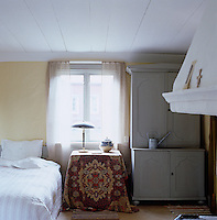 An oriental rug is used to cover the bedside table in this simply furnished bedroom