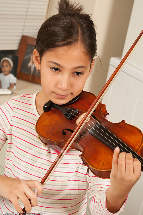 9 year old girl playing musical instrument violin at home
