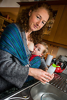 A woman does the washing up while breastfeeding her 20 month old toddler who is in a sling.<br /> <br /> 07/02/2013<br /> Hampshire, England, UK