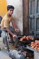 Kathmandu, Nepal.  Nepali Boy Cooking Doughnuts, Durbar Square.