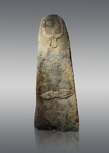 Late European Neolithic prehistoric Menhir standing stone with carvings on its face side. The representation of a stylalised male figure starts at the top with a long nose from which 2 eyebrows arch around the top of the stone. below this is a carving of a falling figure with head at the bottom and 2 curved arms encircling a body above. at the bottom is a carving of a dagger running horizontally across the menhir.  Excavated from Piscina 'E Sali V site,  Laconi. Menhir Museum, Museo della Statuaria Prehistorica in Sardegna, Museum of Prehoistoric Sardinian Statues, Palazzo Aymerich, Laconi, Sardinia, Italy. Grey background.