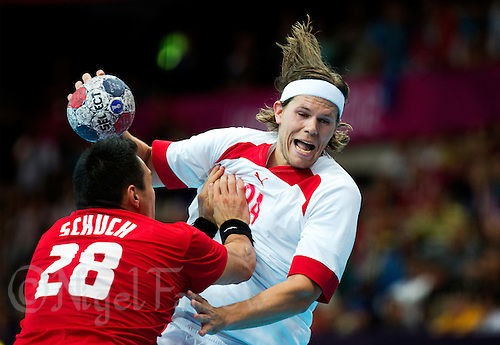 29 JUL 2012 - LONDON, GBR - Mikkel Hansen (DEN) of Denmark (right) shoots during the men's London 2012 Olympic Games Preliminary round handball match against Hungary at The Copper Box in the Olympic Park, in Stratford, London, Great Britain .(PHOTO (C) 2012 NIGEL FARROW)
