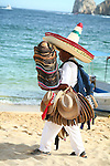 VENDOR CARRIES STACK of STRAW HATS as HE WALKS ALONG the BEACH at CABO SAN LUCAS