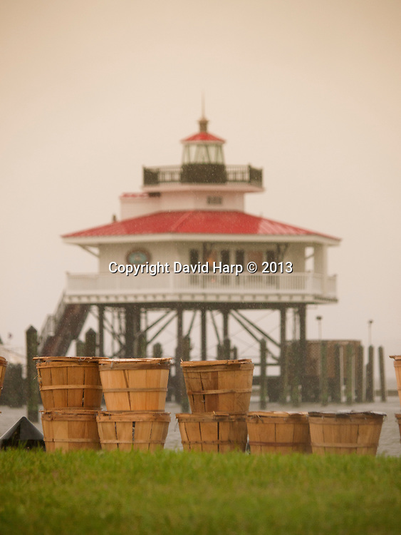 Bushels of blue crabs caught by trotliner off Cambridge arre stacked in front of the reproduction of the lighthouse that once stood sentinel at the mouth of the river.   This lighhouse was  built in 2012.