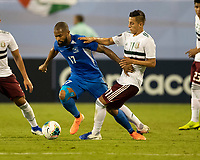 CHARLOTTE, NC - JUNE 23: Cesar Montes #17 defends against Etages Kevin Parsemain #17 during a game between Mexico and Martinique at Bank of America Stadium on June 23, 2019 in Charlotte, North Carolina.