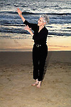 Senior female smiles dancing and exercising on the beach with waves behind her in Los Angeles, California