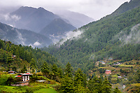 Traditional Bhutanese homes in the rain-cloud clad Begana Valley between Thimpu and Tango Monastery